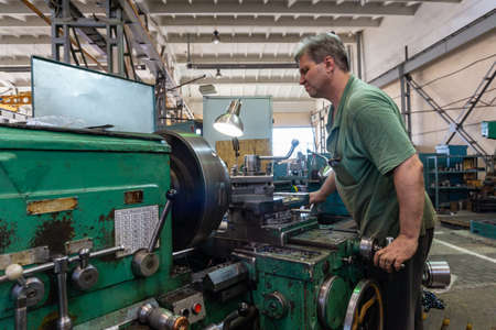 Working man manages the equipment of the cutting machine. Turning work in production