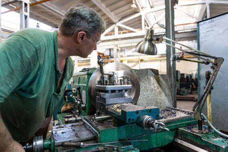 Worker, a man processes metal products on a machine. Turning work in production