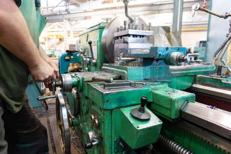 The worker, the man, makes mechanical actions of the machine control. Turning work in production