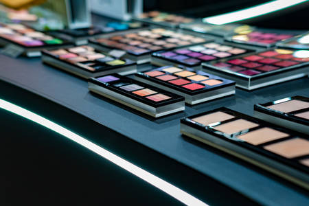 Foto de Cosmetics on the shop window with a variety of colors and shades, mascara, powder, paint for beauty and makeup. Consumerism, retail and purchase concept. - Imagen libre de derechos