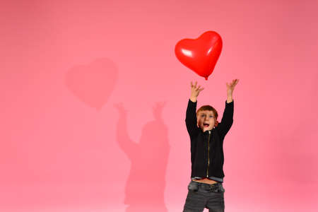Photo for A boy throws and catches a heart-shaped balloon on a pink background in the studio. - Royalty Free Image