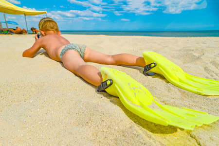 Photo for A cheerful and funny boy in flippers and a mask for scuba diving lies on the sand by the sea and sunbathes in the sun in a clear summer - Royalty Free Image