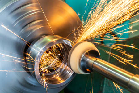 Photo for End processing of a metal surface with an abrasive stone on a circular grinding machine, sparks fly in different directions - Royalty Free Image