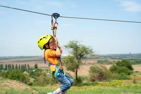 Photo pour A boy dressed in a protective helmet and insurance, goes down the rope, descends holding a protective cable. - image libre de droit