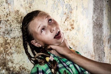 Foto de Strangling a child, a man tries to kill a girl by strangling. - Imagen libre de derechos