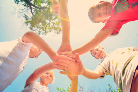 Photo pour Friends hold hands together, bottom view of a group of people clasped hands. - image libre de droit