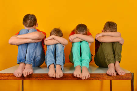 Photo for Barefoot children sit with their legs crossed and hugging their knees. Four children lowered their heads down - Royalty Free Image