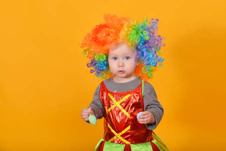 Photo for A small child, a girl in a clown wig, holds Easter eggs in her hands - Royalty Free Image
