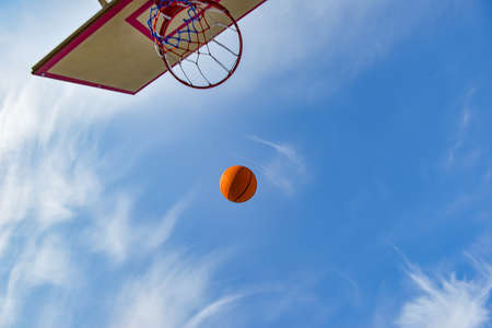 Photo pour A basketball ball flies into a hoop with a net against a blue cloudy sky. Sports activities on the playground - image libre de droit