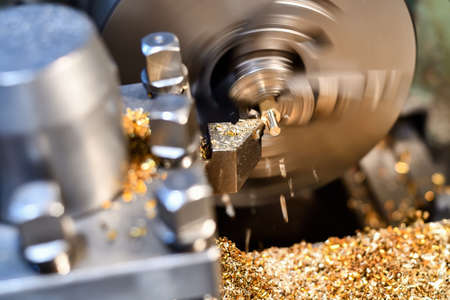Photo pour Processing of non-ferrous metal by cutting on a lathe. Manufacturing of parts from bronze and brass. - image libre de droit