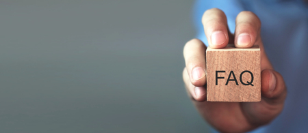 Photo pour Man holding FAQ message on wooden cube. Frequently Asked Questions - image libre de droit