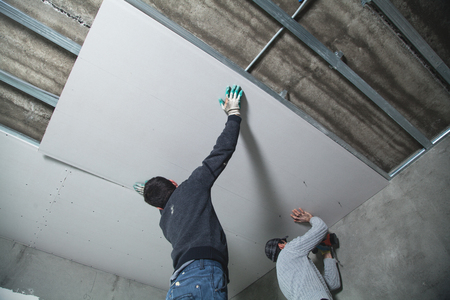 Photo for Workers fitting panel into frame of ceiling. - Royalty Free Image