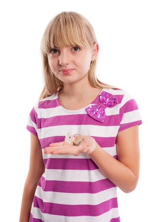 Nice teen girl holding a hearing aid in front of a white background.