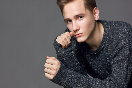 a young man in a gray sweater on a gray background studio