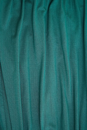 Abstract background texture of a length of bluey green hanging rough textured woven textile falling in folds,