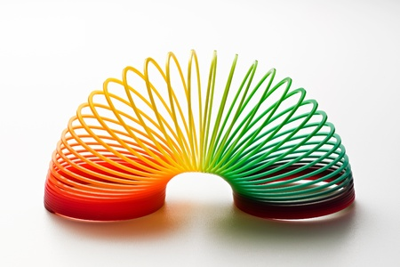 Rainbow coloured slinky toy made of a plastic wire spiral coil which enables flexibility and mobility