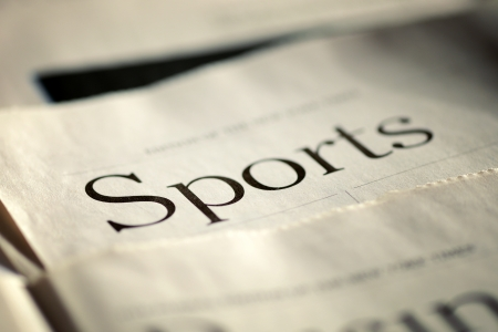 Edition of the daily newspaper with selective focus to the header in the Sports section lying flat on a table, low angle