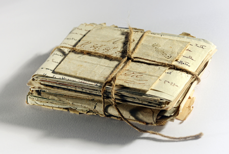 Pile of old aged worn letters and correspondence tied into a bundle with string, high angle view on a white background