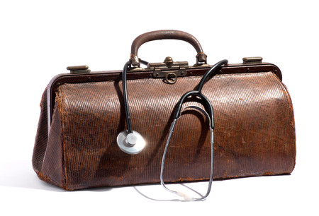 Old brown leather doctors bag with a stethoscope looped around the handle in a medical and healthcare concept, on a white background