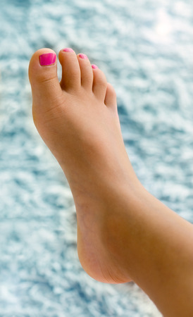 Girl Foot with Pink Nail Polish on Toenails Against Blue Background
