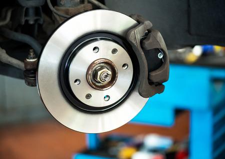 Brand new brake disc on car in a garage