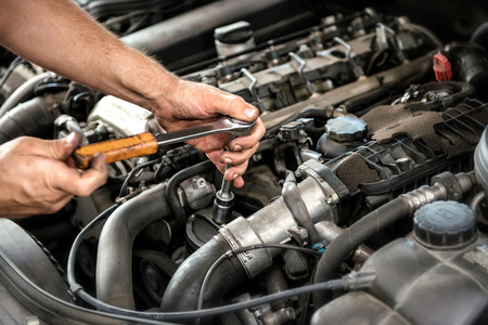 Photo pour Mechanic using a wrench and socket on the engine of a motor car during a service or repair in an automotive workshop, close up of his hands - image libre de droit