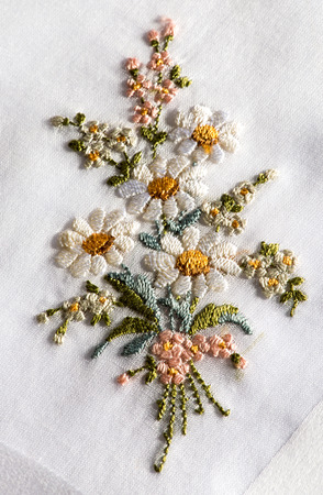 Photo pour Decorative embroidery on a white textile of a bouquet of flowers with white spring or summer daisies in a handicraft and needlework concept - image libre de droit