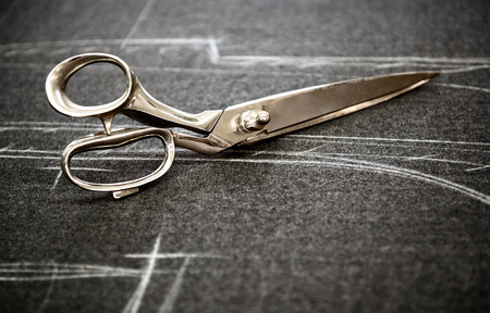 Tailors scissors lying on fabric marked in chalk with the pattern of the garment in a close up view with copyspace