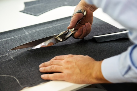Tailor cutting out the marked pattern on dark fabric with large scissors on the workbench in his shop, close up view of his hands