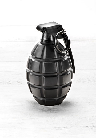 Grenade standing upright with the pin safely in position on a white wooden board in a close up view