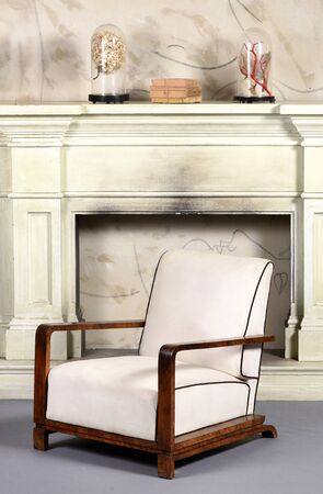 Art Deco style upholstered white armchair with typical angular wooden armrests and low slung design in front of an old smoky fireplace