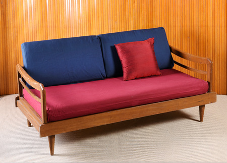 Upholstered red and blue vintage sofa with a wooden frame and armrests in a wood panelled room