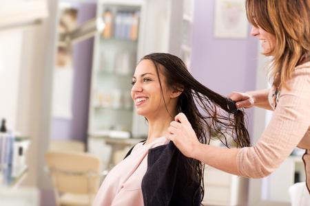 Foto für Smiling brunette woman having her hair combing after wash by professional stylist hairdresser in beauty saloon. Side portrait with copy space - Lizenzfreies Bild