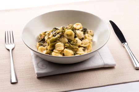 Foto de Orecchiette con Cime di Rapa, or a bowl of orecchiette pasta with broccoli rabe, a regional dish from Puglia, Italy served in a bowl at table - Imagen libre de derechos