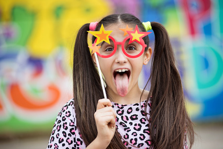 Photo pour Fun young girl sticking out her tongue as she holds a party accessory of colorful glasses with stars to her eyes against a multicolored background - image libre de droit