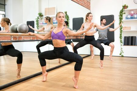 Group of people performing second position plie exercises using the booty barre in a gym reflected in the mirror alongside in a health and fitness concept