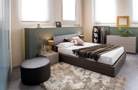 Photo pour Modern luxury brown monochrome bedroom interior with large headboard above a double beds with cabinets, ottoman and built in wardrobe - image libre de droit