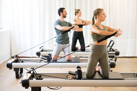 Photo for Three people exercising torson rotation at gym using pilates reformer beds - Royalty Free Image