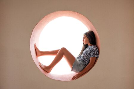 Young barefoot girl curled inside a round opening in a cement wall relaxing looking outside with a thoughtful expression