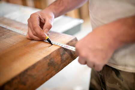 Photo pour Woodworker taking measurement with a measuring tape marking the length on a wooden plank with a marker in a close up on his hands - image libre de droit