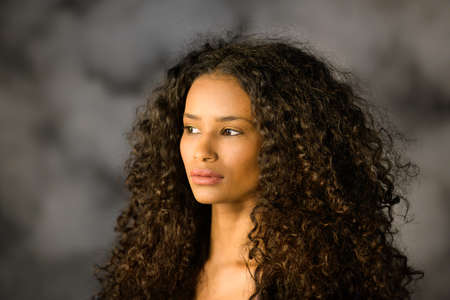 Photo for Headshot of a beautiful thoughtful black girl with long curly hair looking off to the side with a pensive serious expression - Royalty Free Image