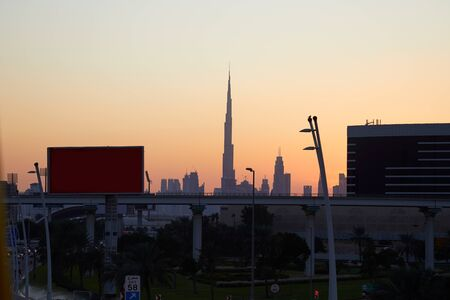 Photo for Dubai skyline with Burj Khalifa skyscraper at sunset, clear sky with flyover, billboards and street in United Arab Emirates - Royalty Free Image