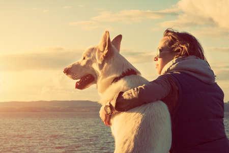 Foto de Young attractive girl with her pet dog at a beach, colorised image - Imagen libre de derechos