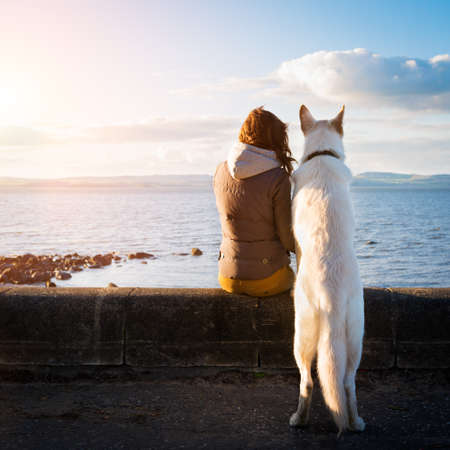 Foto de Young girl with her pet dog at a seaside - Imagen libre de derechos