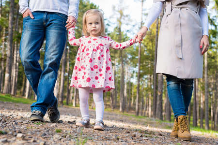 Happy young family taking a walk in a park, family holding hands walking together along forrest path