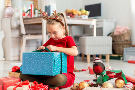 Photo pour Cute super excited young girl opening large christmas present while sitting on living room floor. Candid family christmas time lifestyle background. - image libre de droit