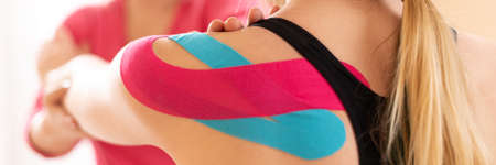 Photo pour Kinesiology, physical therapy, rehabilitation banner. Female patient wearing kinesio tape on her shoulder exercising with a professional physical therapist. Close up. - image libre de droit