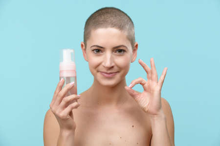 Photo for Studio portrait of a young woman holding a bottle of gentle foam facial cleanser. Beauty products and skin care concept. - Royalty Free Image
