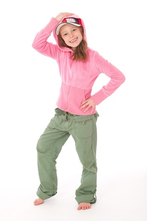 Sporty girl in pink top and green trousers with cap and hood and hand on head