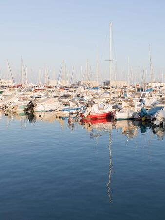 El Campello - 2 October 2015: fishing port and many fishing boats are on the quays of El Campello evening and beautifully reflected in the water 2 October 2015, El Campello, Spain